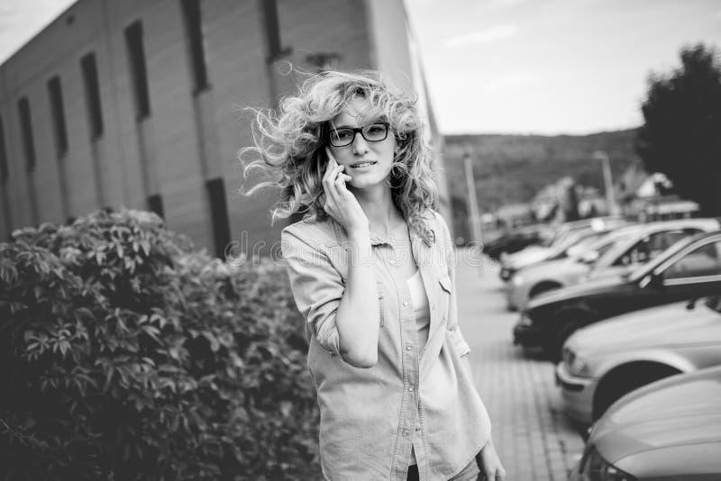 Mujer de negocios confiada joven que camina en la prisa, hablando en el teléfono móvil en la calle de la ciudad fotos de archivo