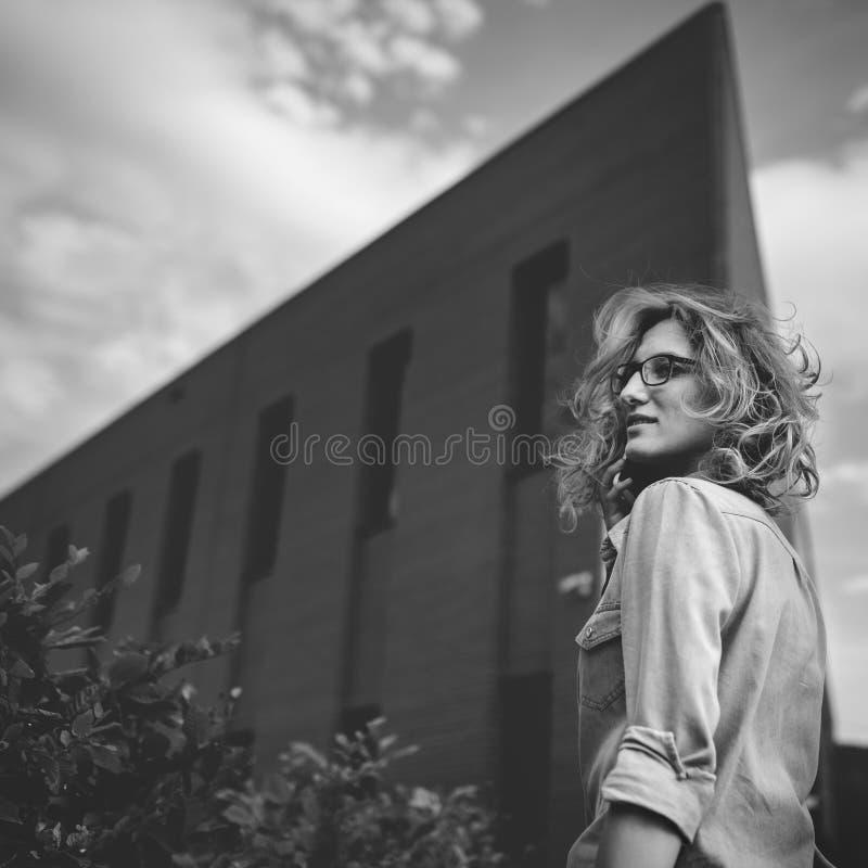 Mujer de negocios confiada joven que camina en la prisa, hablando en el teléfono móvil en la calle de la ciudad foto de archivo libre de regalías
