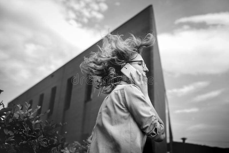 Mujer de negocios confiada joven que camina en la prisa, hablando en el teléfono móvil en la calle de la ciudad foto de archivo