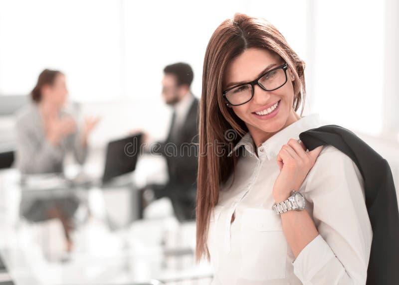 Mujer de negocios confiada que se coloca con una chaqueta sobre su shoulde fotografía de archivo libre de regalías