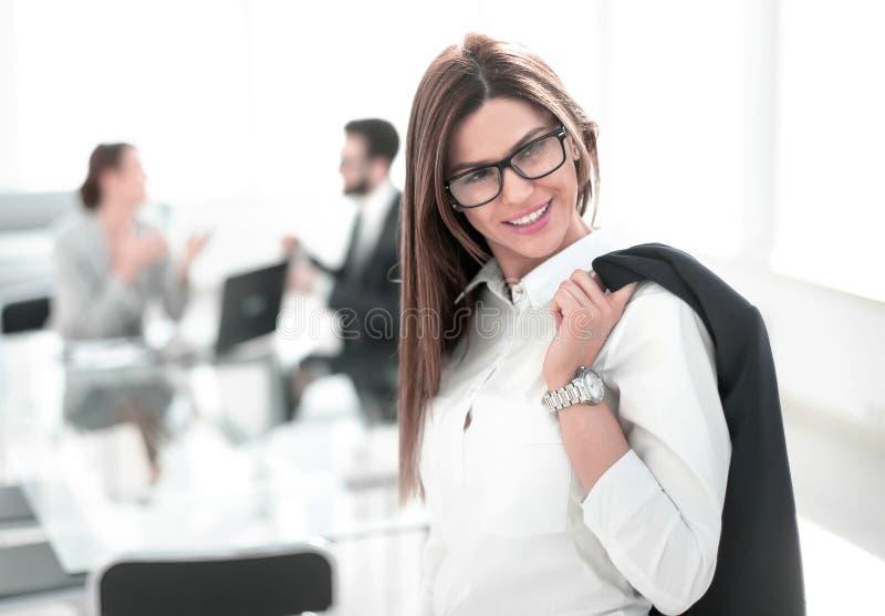 Mujer de negocios confiada que se coloca con una chaqueta sobre su shoulde foto de archivo libre de regalías
