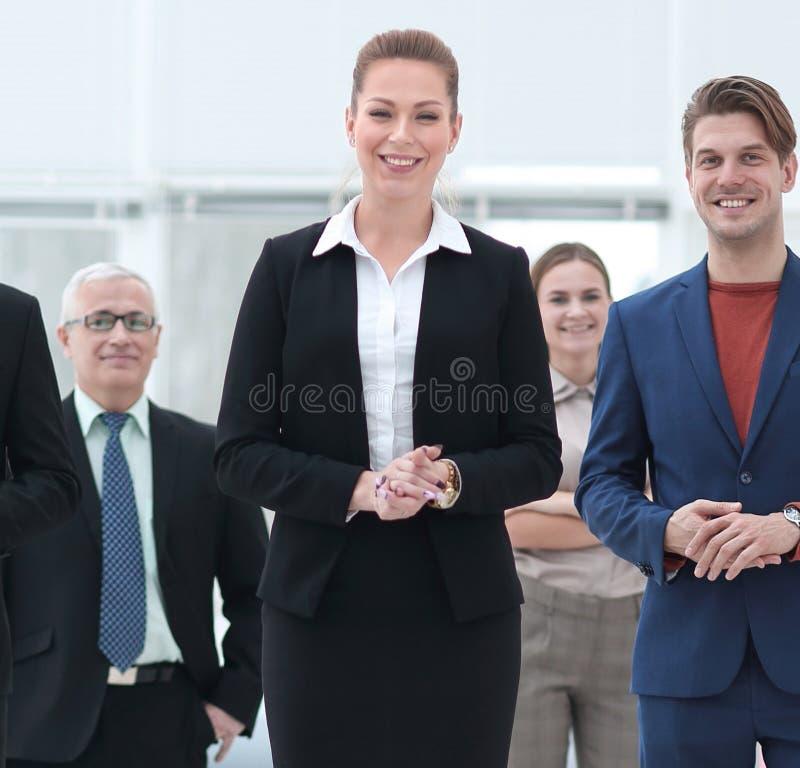 Mujer de negocios confiada que se coloca delante de su equipo del negocio imágenes de archivo libres de regalías
