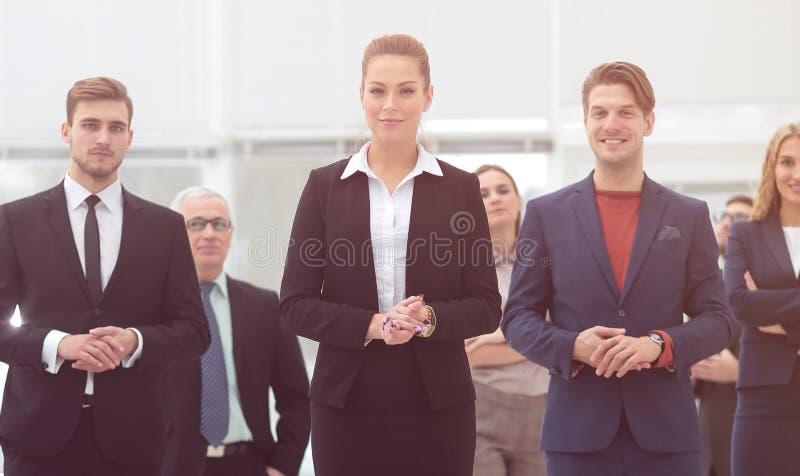 Mujer de negocios confiada que se coloca delante de su equipo del negocio foto de archivo libre de regalías