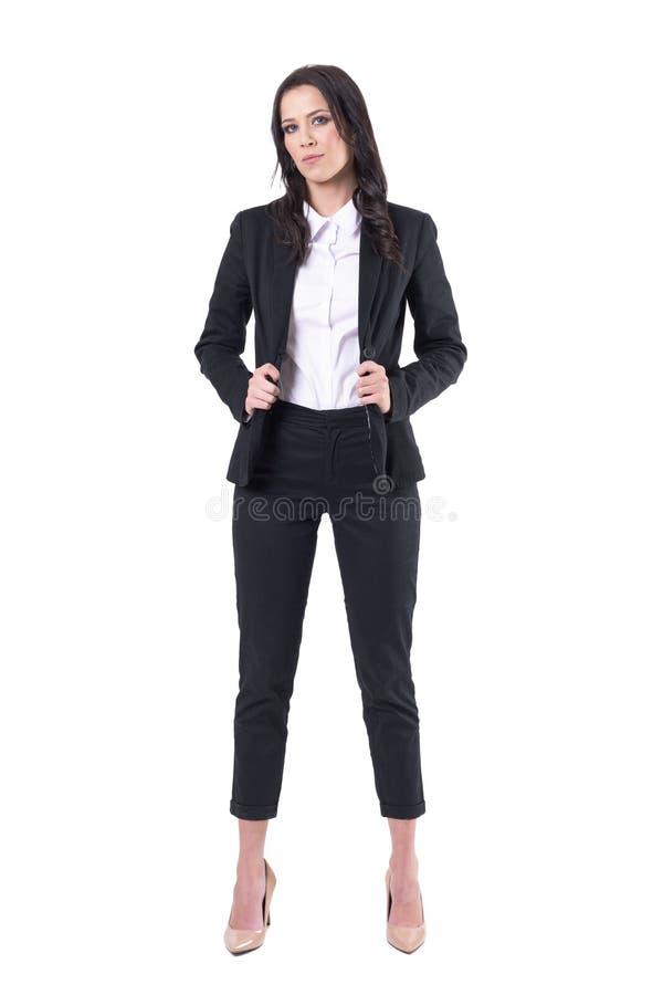 Mujer de negocios confiada seria en la moda formal del estilo que presenta y que mira la cámara fotos de archivo