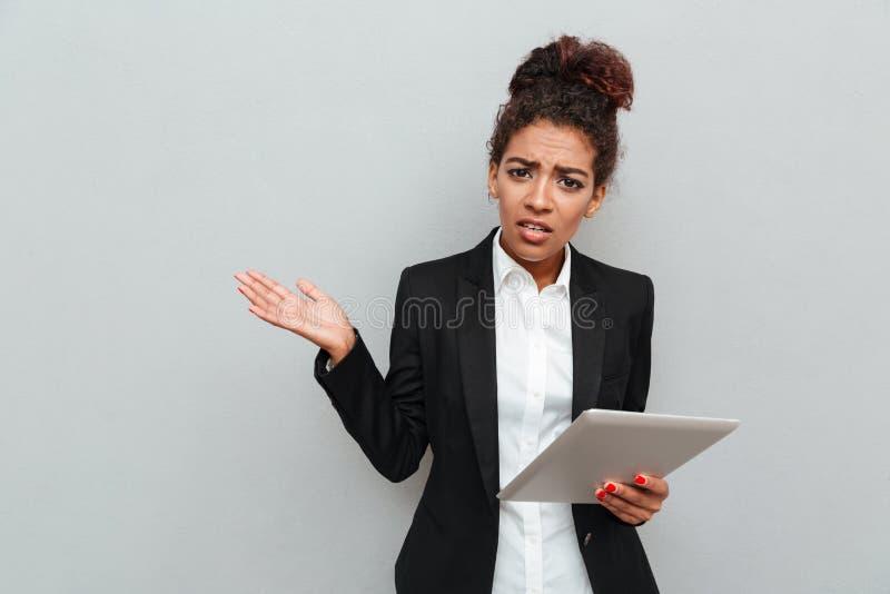 Mujer de negocios confusa africana joven que sostiene la tableta imagen de archivo