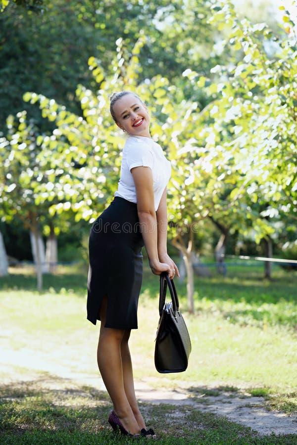 Mujer de negocios coqueta que sostiene un bolso fotos de archivo libres de regalías