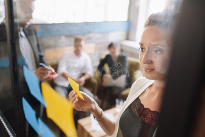 Mujer de negocios creativa que pega notas adhesivas en la pared de cristal fotos de archivo