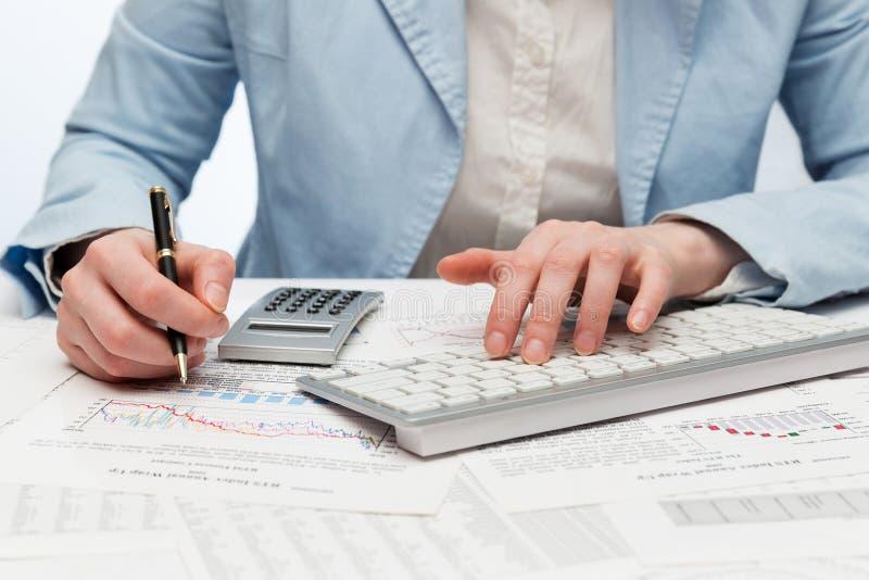 Mujer de negocios de la contabilidad financiera que usa el teclado de ordenador foto de archivo