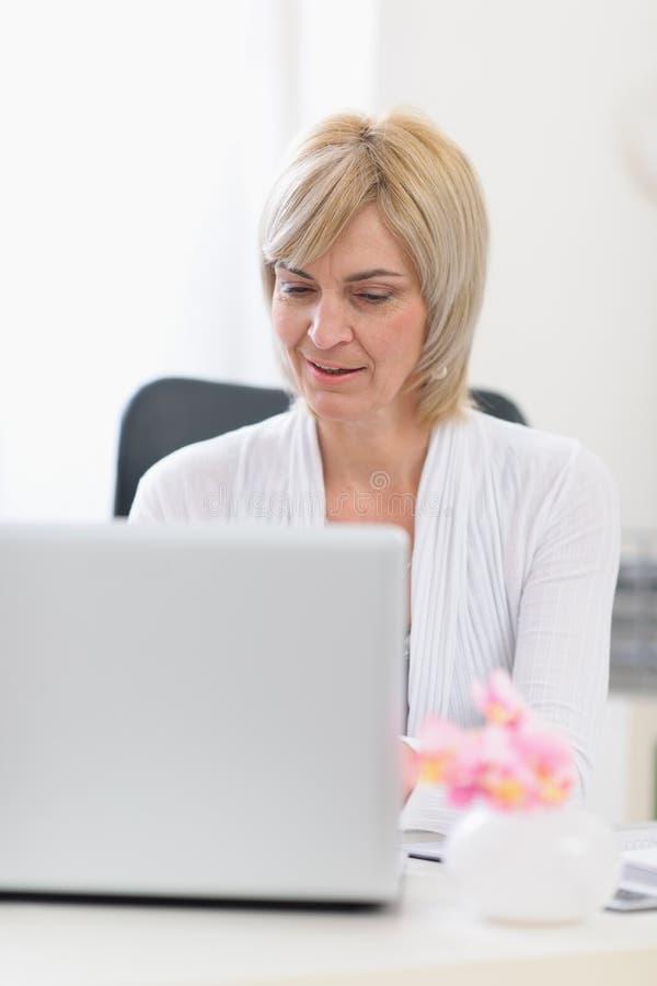 Mujer de negocios de la Edad Media que trabaja en la computadora portátil foto de archivo