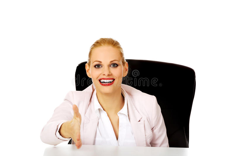 Mujer de negocios de la sonrisa que se sienta detrás del escritorio con una mano abierta lista para el apretón de manos fotos de archivo