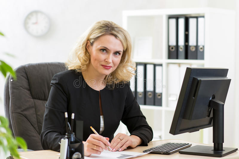 Mujer de negocios de mediana edad que trabaja en la PC en oficina foto de archivo libre de regalías