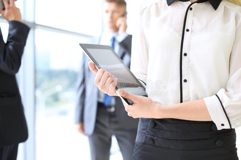 Mujer de negocios desconocida que usa la tableta en pasillo de la oficina entre empresarios imagen de archivo