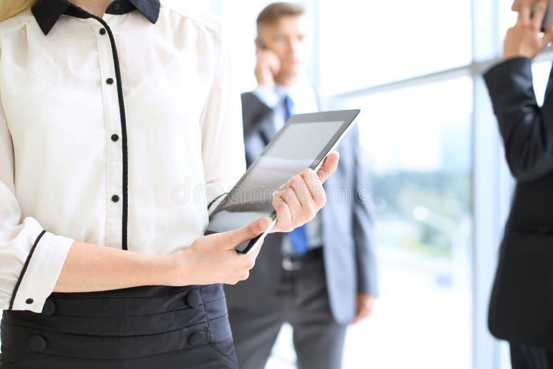 Mujer de negocios desconocida que usa la tableta en pasillo de la oficina entre empresarios fotos de archivo libres de regalías