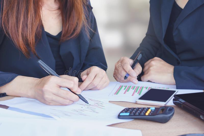 Mujer de negocios de dos asiáticos que habla y que trabaja junto en la oficina incluyendo el gráfico financiero, calculadora fotografía de archivo