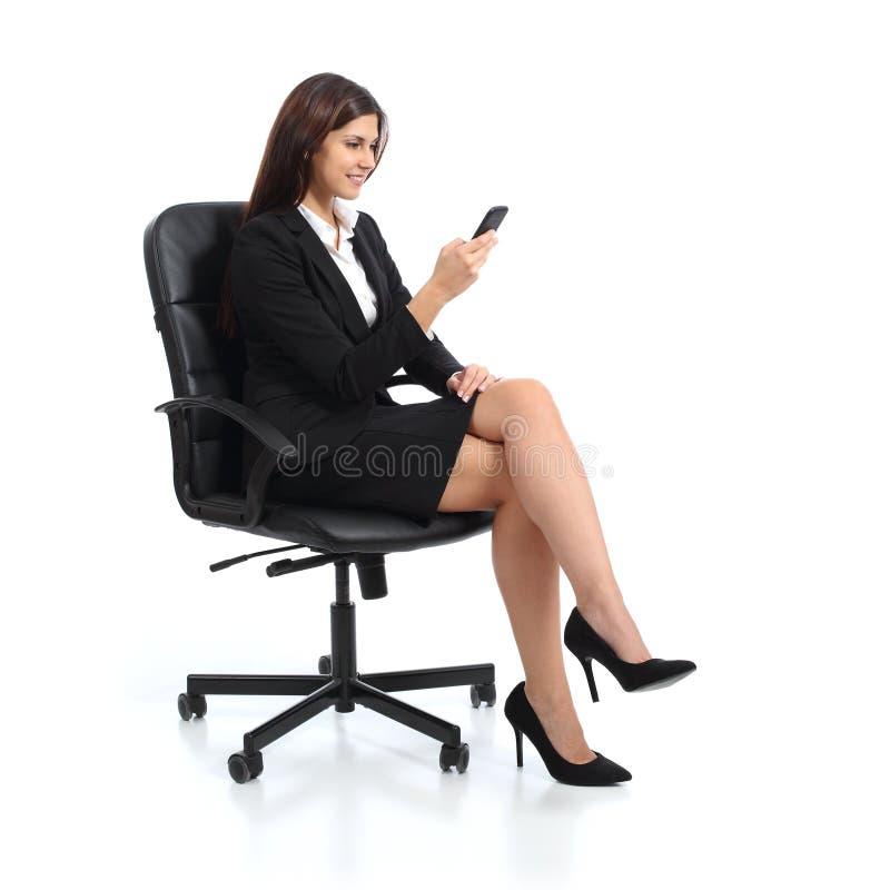 Mujer de negocios ejecutiva que usa un teléfono elegante que se sienta en una silla imagen de archivo libre de regalías