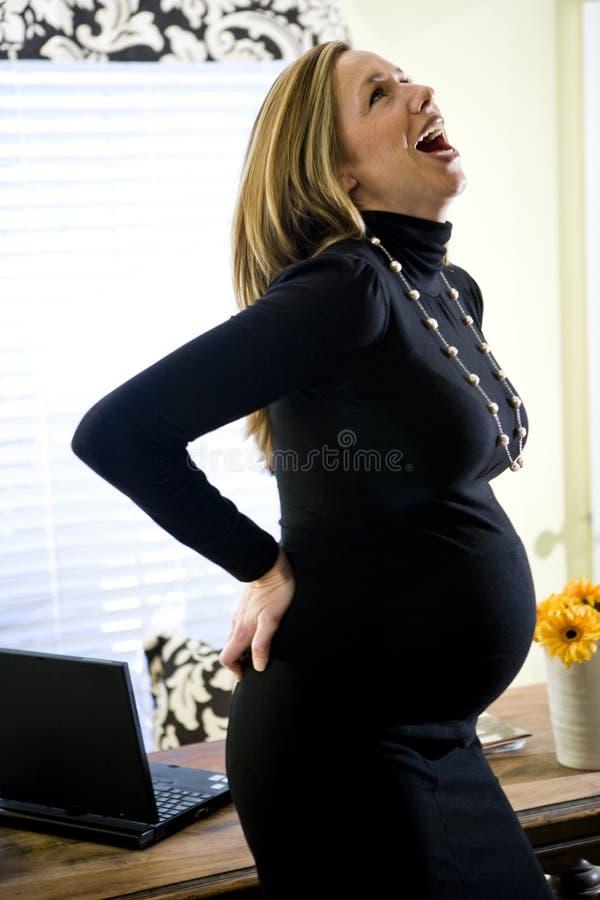 Mujer de negocios embarazada que ríe hacia fuera la carga imagenes de archivo