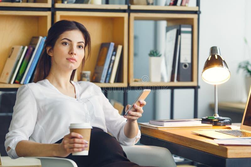 Mujer de negocios embarazada que trabaja en el café de consumición que se sienta de la maternidad de la oficina imagenes de archivo