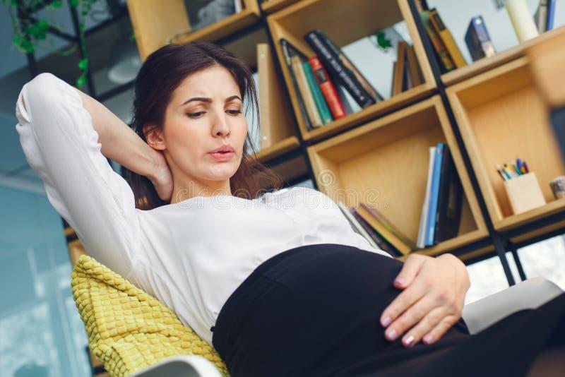 Mujer de negocios embarazada que trabaja en el dolor del vientre de la maternidad de la oficina que se sienta fotos de archivo