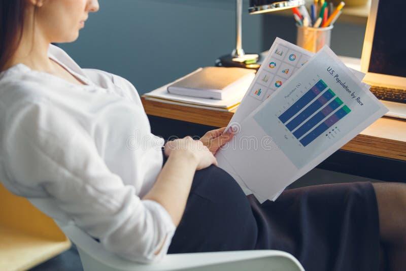 Mujer de negocios embarazada que trabaja en el informe de la lectura de la maternidad de la oficina que se sienta imagenes de archivo