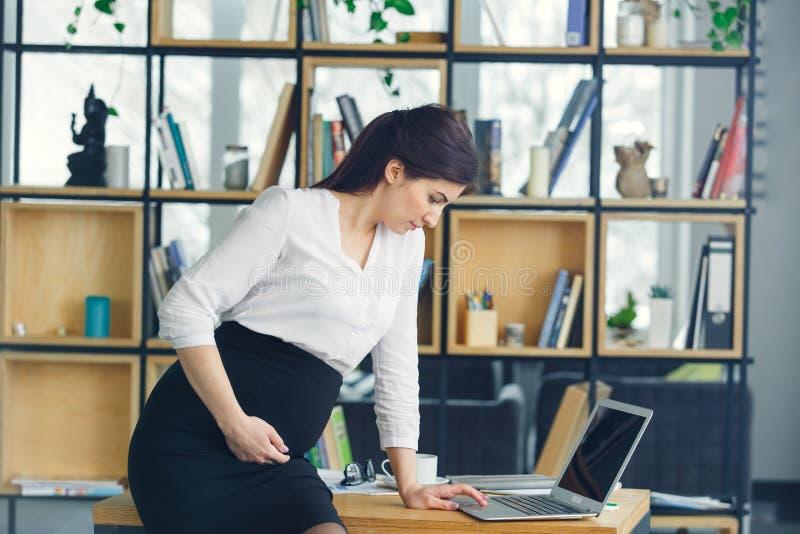 Mujer de negocios embarazada que trabaja en el ordenador portátil de la ojeada de la maternidad de la oficina fotografía de archivo libre de regalías