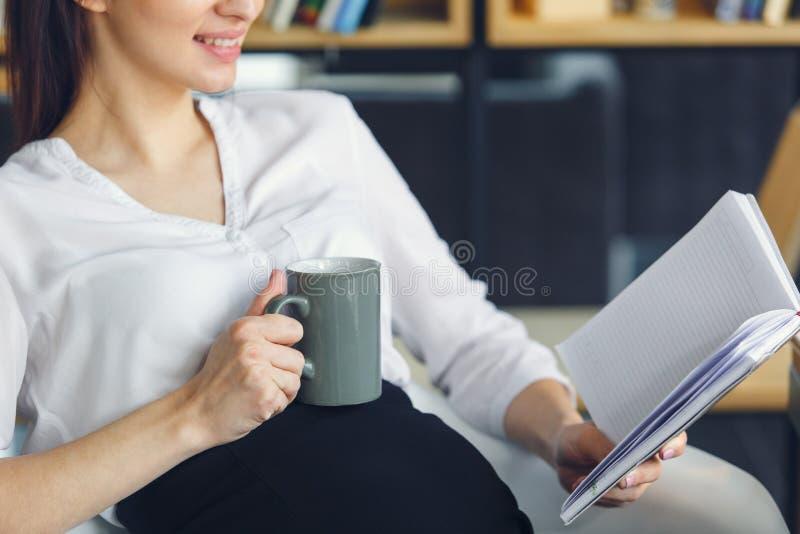 Mujer de negocios embarazada que trabaja en el primer del libro de lectura de la maternidad de la oficina que se sienta imagenes de archivo