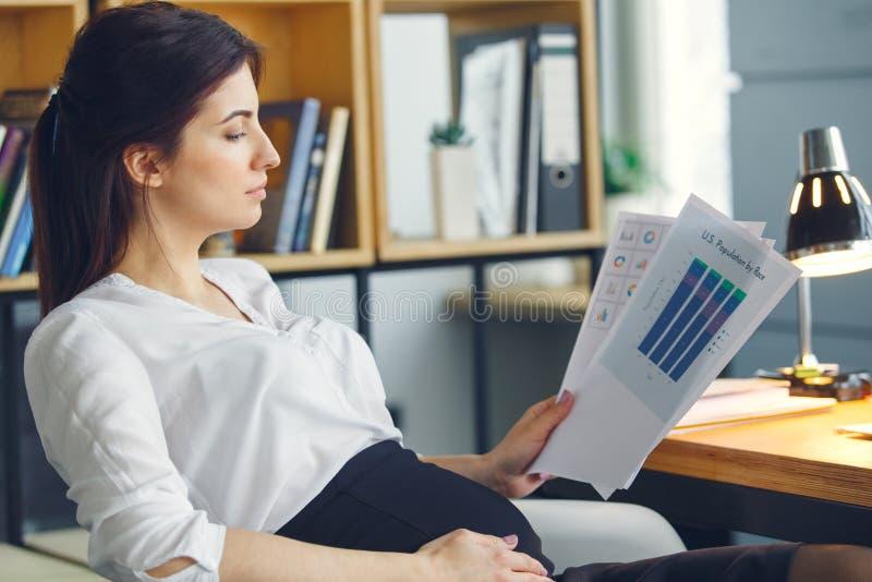 Mujer de negocios embarazada que trabaja en el proyecto de la lectura de la maternidad de la oficina que se sienta foto de archivo