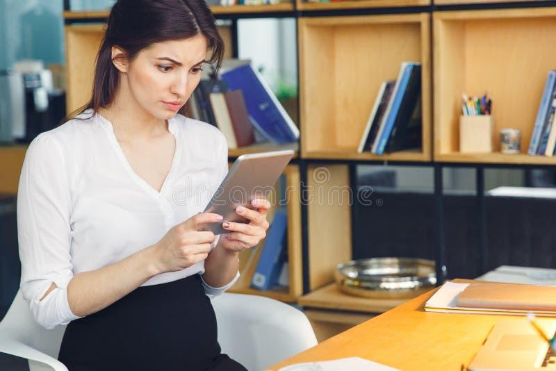 Mujer de negocios embarazada que trabaja en el vídeo de observación que se sienta de la maternidad de la oficina en la tableta di fotografía de archivo libre de regalías