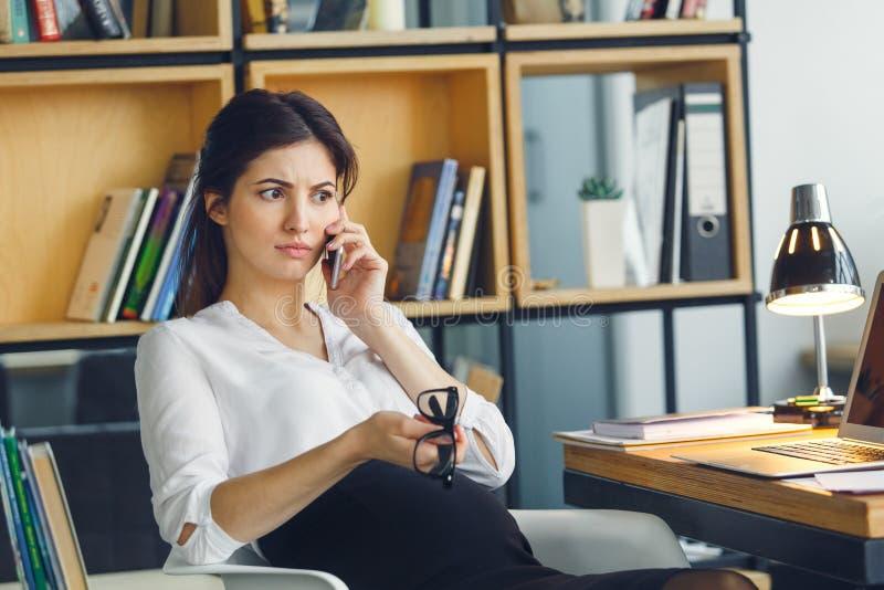 Mujer de negocios embarazada que trabaja en la conversación telefónica que se sienta de la maternidad de la oficina fotografía de archivo libre de regalías