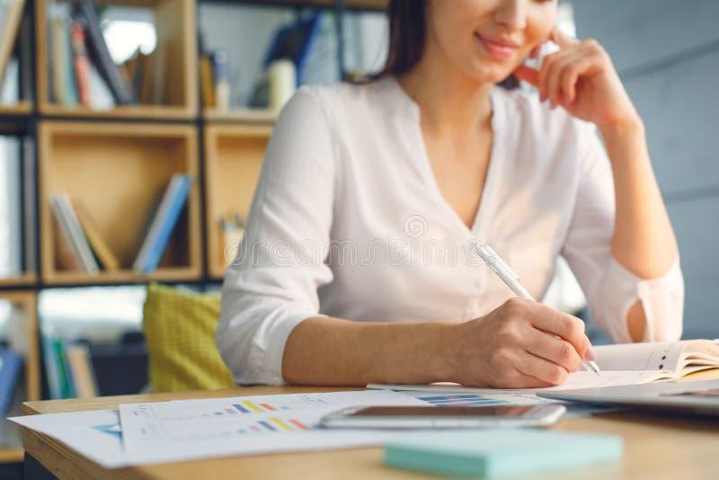 Mujer de negocios embarazada que trabaja en la escritura que se sienta de la maternidad de la oficina en cuaderno imágenes de archivo libres de regalías