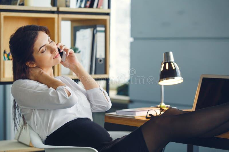 Mujer de negocios embarazada que trabaja en la llamada de teléfono de contestación de la maternidad de la oficina que se sienta fotos de archivo