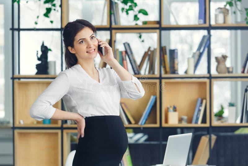 Mujer de negocios embarazada que trabaja en la llamada de teléfono de contestación permanente de la maternidad de la oficina imagen de archivo