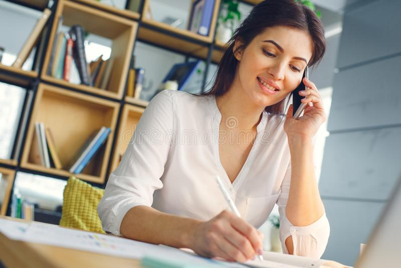Mujer de negocios embarazada que trabaja en la llamada de teléfono de la maternidad de la oficina que se sienta fotos de archivo libres de regalías