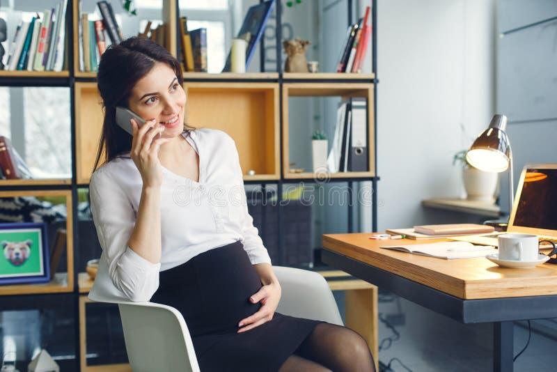 Mujer de negocios embarazada que trabaja en la llamada de teléfono de la maternidad de la oficina que se sienta imágenes de archivo libres de regalías