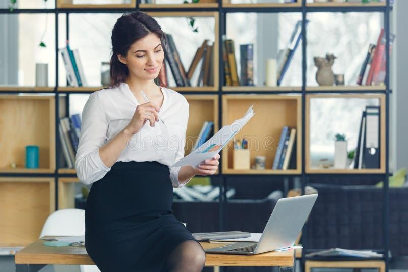 Mujer de negocios embarazada que trabaja en la maternidad de la oficina que lleva a cabo documentos imagen de archivo libre de regalías