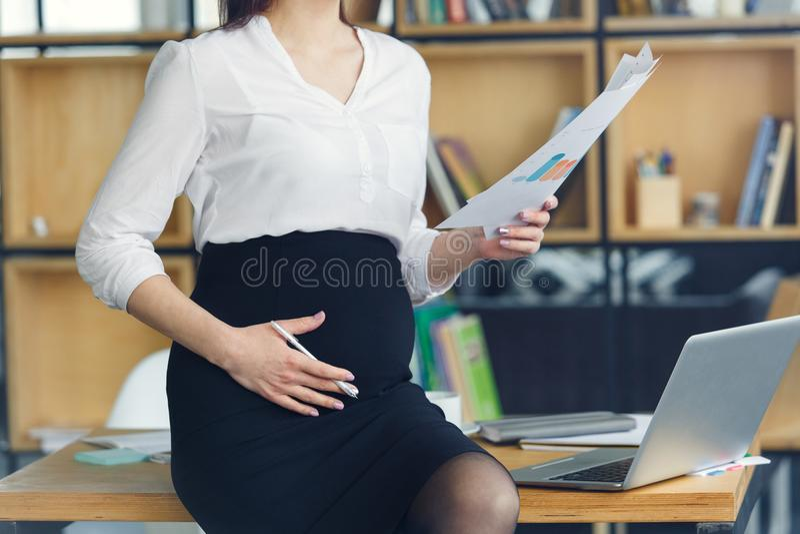 Mujer de negocios embarazada que trabaja en la maternidad de la oficina que lleva a cabo informe imagen de archivo libre de regalías