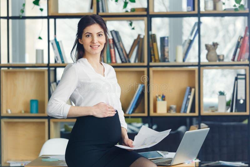 Mujer de negocios embarazada que trabaja en la maternidad de la oficina que se coloca de mirada de la sonrisa de la cámara fotografía de archivo libre de regalías
