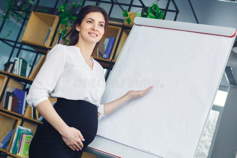 Mujer de negocios embarazada que trabaja en la maternidad de la oficina que se coloca que muestra datos imagenes de archivo