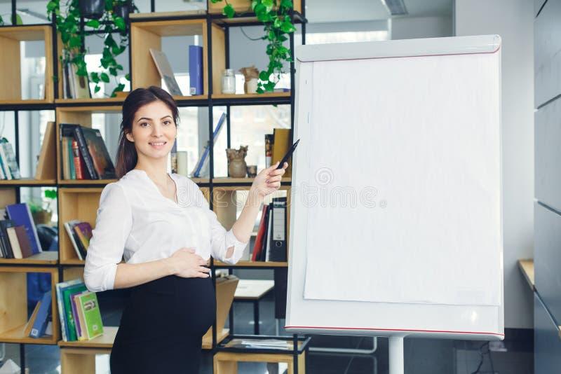 Mujer de negocios embarazada que trabaja en la maternidad de la oficina que se coloca de presentación de la información fotos de archivo libres de regalías