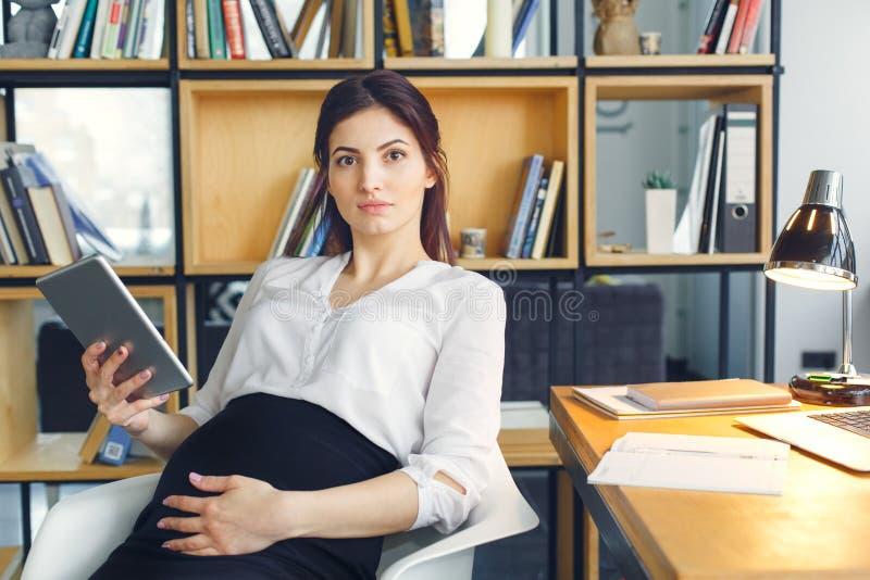 Mujer de negocios embarazada que trabaja en la maternidad de la oficina que se sienta con la tableta digital imagen de archivo libre de regalías