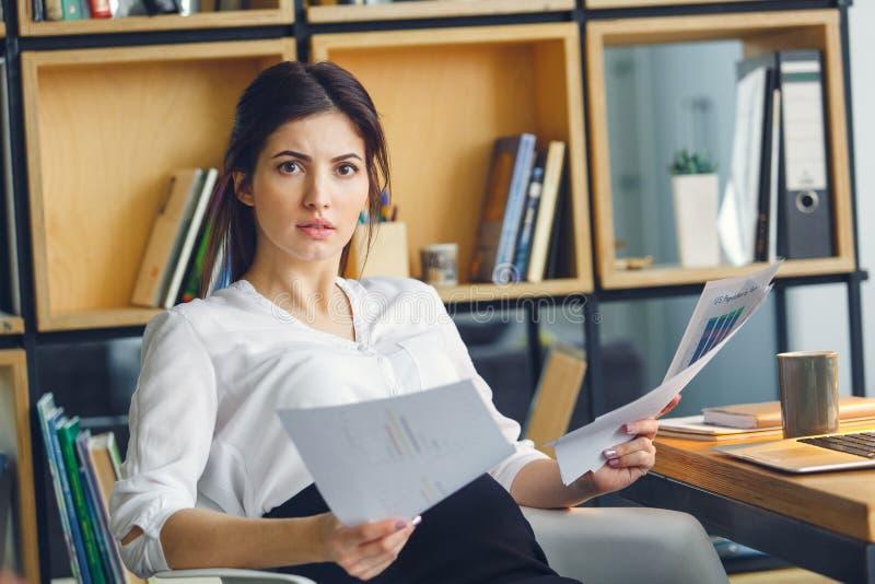 Mujer de negocios embarazada que trabaja en la maternidad de la oficina que se sienta llevando a cabo documentos foto de archivo libre de regalías