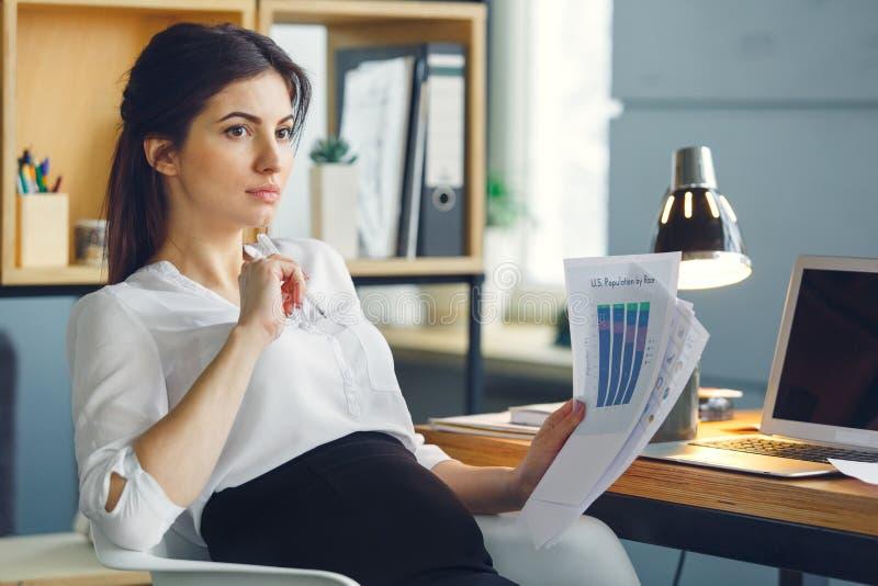 Mujer de negocios embarazada que trabaja en la maternidad de la oficina que se sienta llevando a cabo informe fotos de archivo libres de regalías