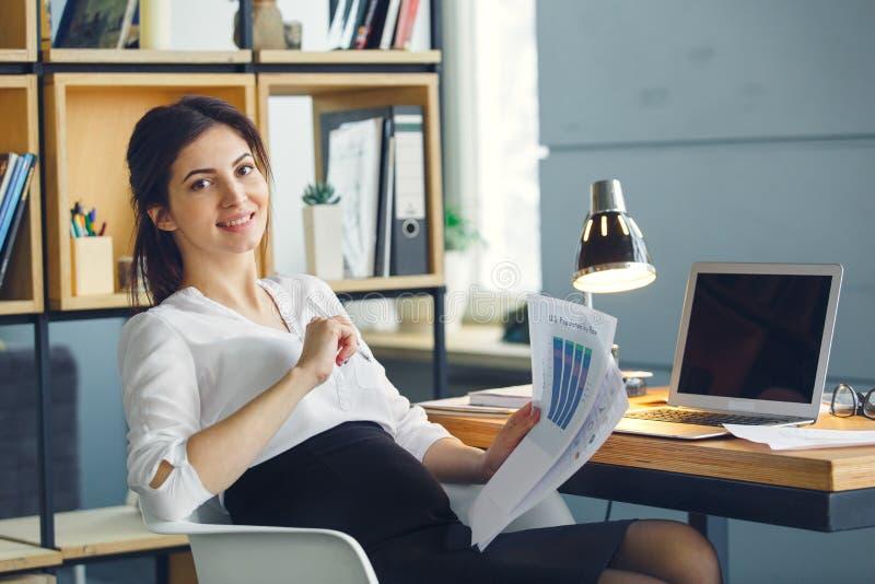 Mujer de negocios embarazada que trabaja en la maternidad de la oficina que se sienta llevando a cabo informe del proyecto fotos de archivo