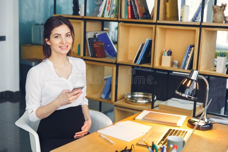 Mujer de negocios embarazada que trabaja en la maternidad de la oficina que se sienta sosteniendo smartphone imagen de archivo