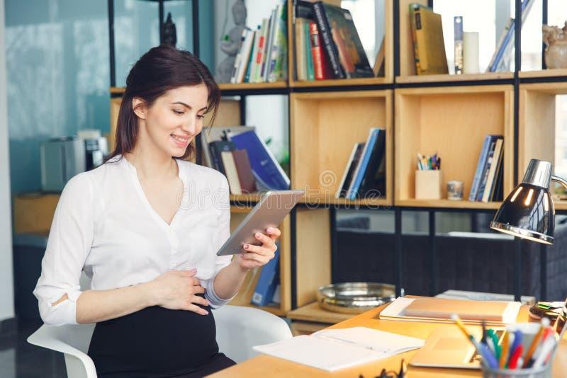 Mujer de negocios embarazada que trabaja en la maternidad de la oficina que se sienta sosteniendo la tableta digital fotografía de archivo libre de regalías