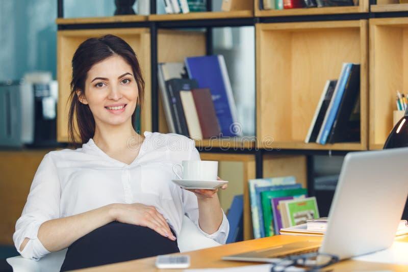Mujer de negocios embarazada que trabaja en la maternidad de la oficina que se sienta sosteniendo la taza de café fotos de archivo