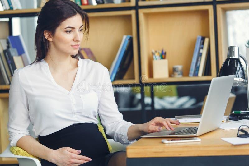 Mujer de negocios embarazada que trabaja en la maternidad de la oficina que se sienta usando el ordenador portátil imagenes de archivo