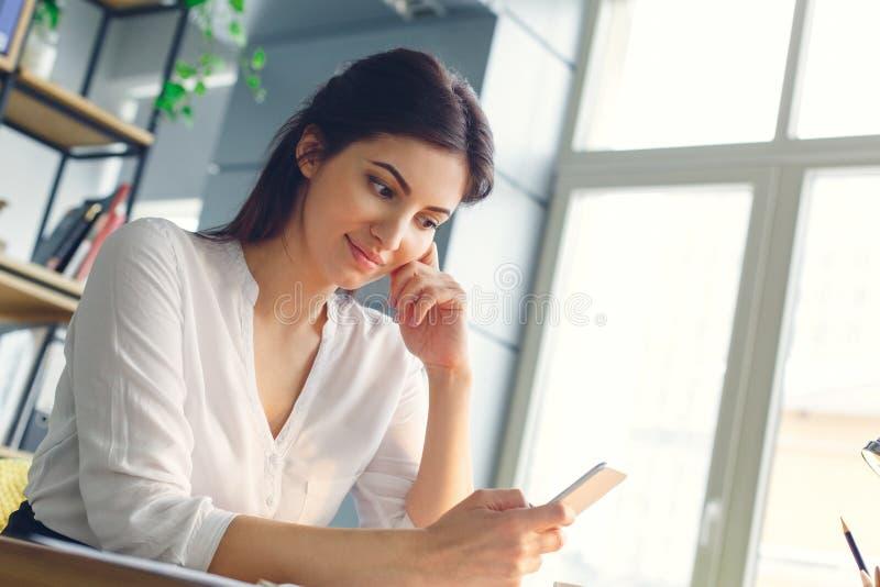 Mujer de negocios embarazada que trabaja en la maternidad de la oficina que se sienta usando smartphone imagen de archivo libre de regalías