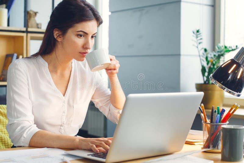 Mujer de negocios embarazada que trabaja en la maternidad de la oficina que se sienta usando té de consumición del ordenador port imágenes de archivo libres de regalías