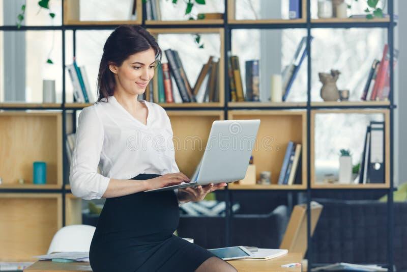 Mujer de negocios embarazada que trabaja en la maternidad de la oficina que sostiene el ordenador portátil foto de archivo