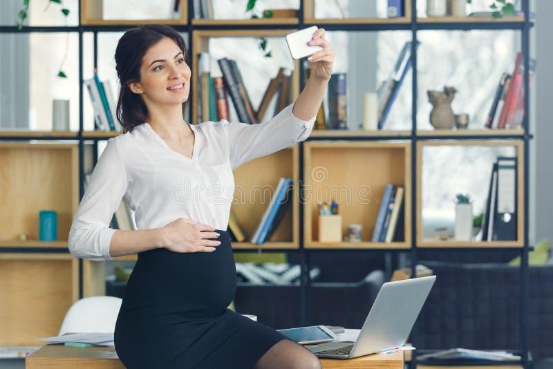 Mujer de negocios embarazada que trabaja en la maternidad de la oficina que toma las fotos del selfie fotografía de archivo libre de regalías